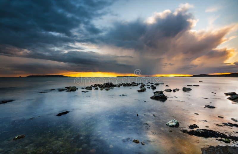 Puesta del sol debajo de las nubes de tormenta en la costa de Dorset imagen de archivo libre de regalías