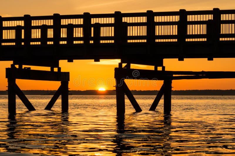 Puesta del sol debajo del paseo marítimo fotografía de archivo libre de regalías