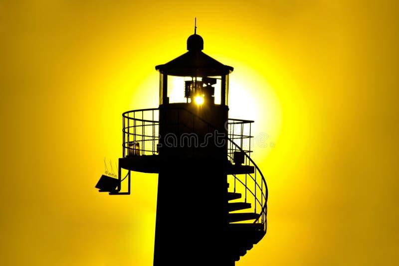 Puesta del sol del amarillo del silhouetteat del faro foto de archivo libre de regalías