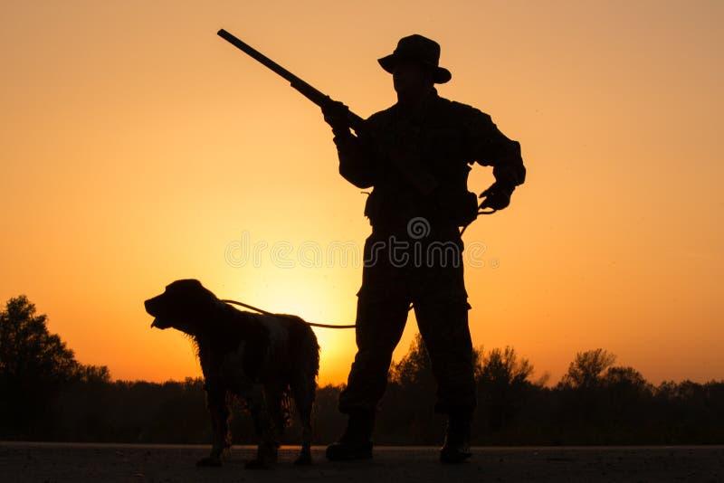 Puesta del sol del cazador con un perro imagen de archivo libre de regalías