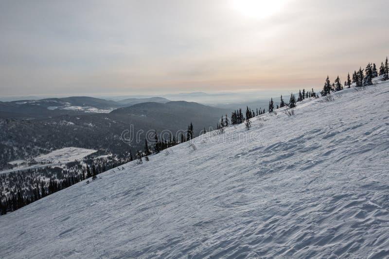Puesta del sol del invierno de la nieve de la cuesta de montaña fotos de archivo libres de regalías