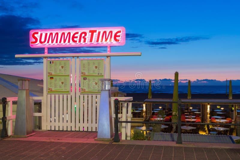 Puesta del sol del mar con la entrada a una tienda del partido de la playa a lo largo de la costa holandesa fotografía de archivo