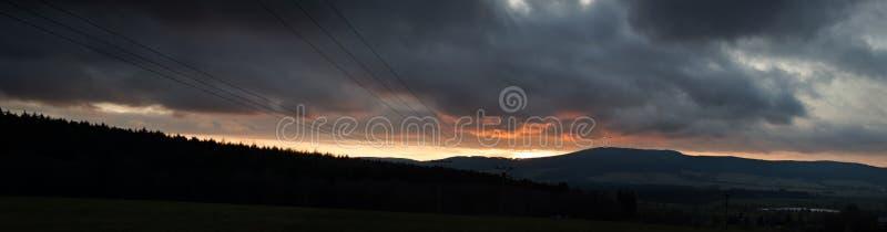 Puesta del sol del panorama sobre las montañas al cielo cubierto foto de archivo libre de regalías