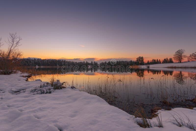 Puesta del sol del pequeño lago idílico en el invierno imagenes de archivo