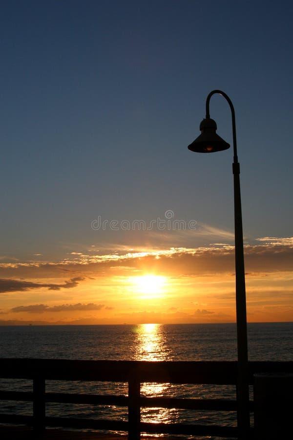 Puesta del sol del poste de la lámpara del embarcadero fotografía de archivo