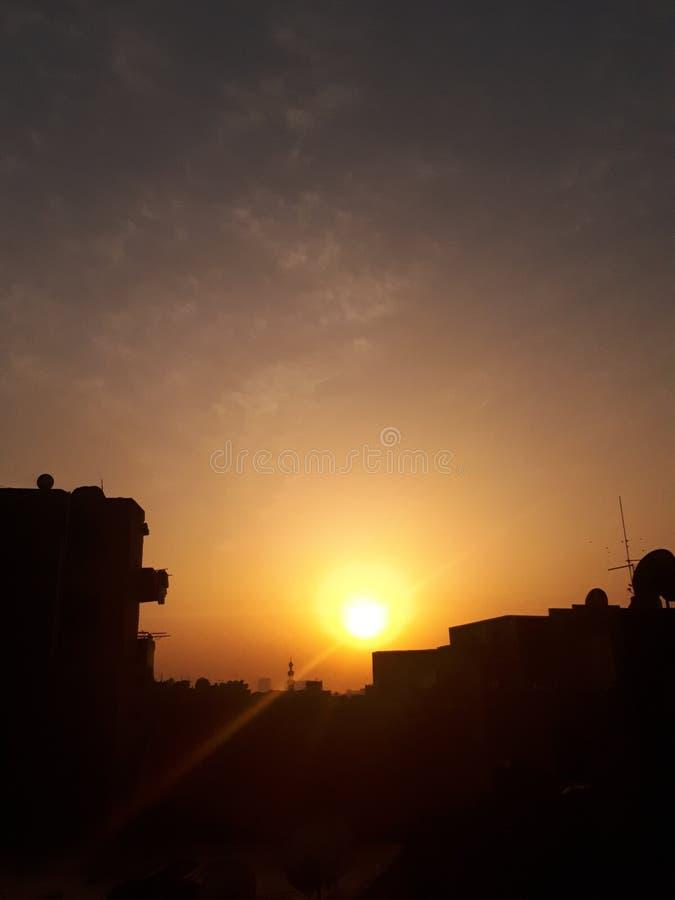 Puesta del sol delante de hogares fotos de archivo