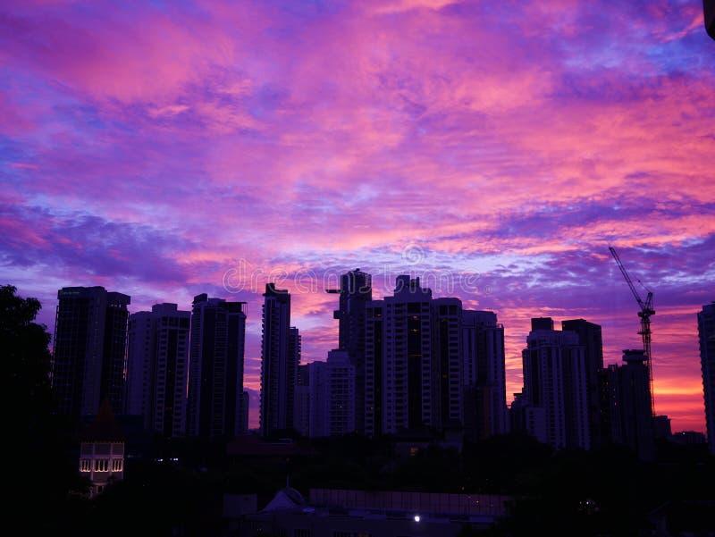 Puesta del sol detrás de edificios con el cielo nublado hermoso fotografía de archivo