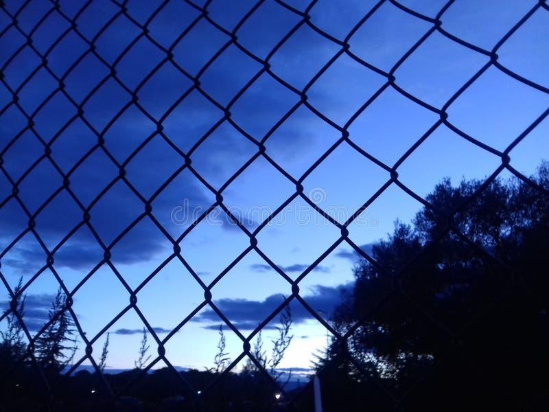 Puesta del sol detrás de la cerca foto de archivo