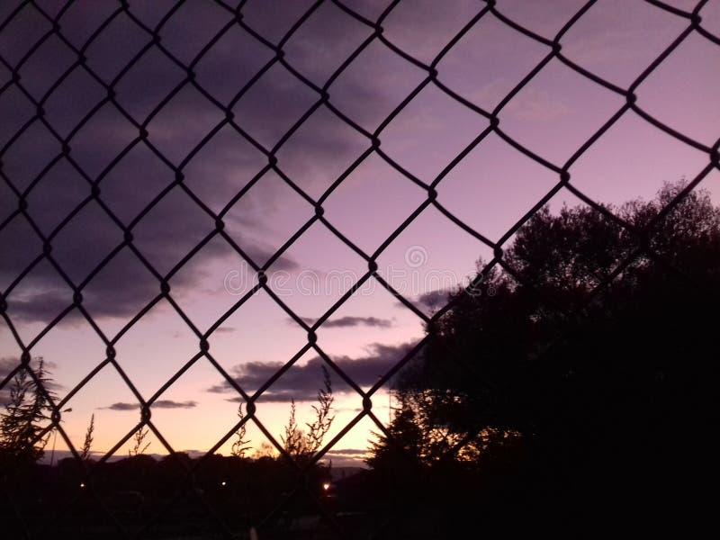 Puesta del sol detrás de la cerca imagen de archivo