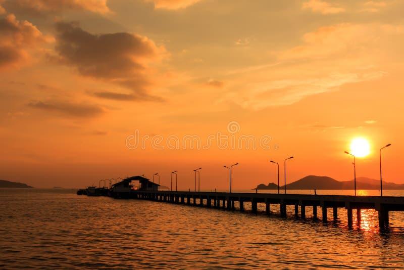 Puesta del sol detrás de la pequeños nave del puerto y posts de la lámpara imagenes de archivo