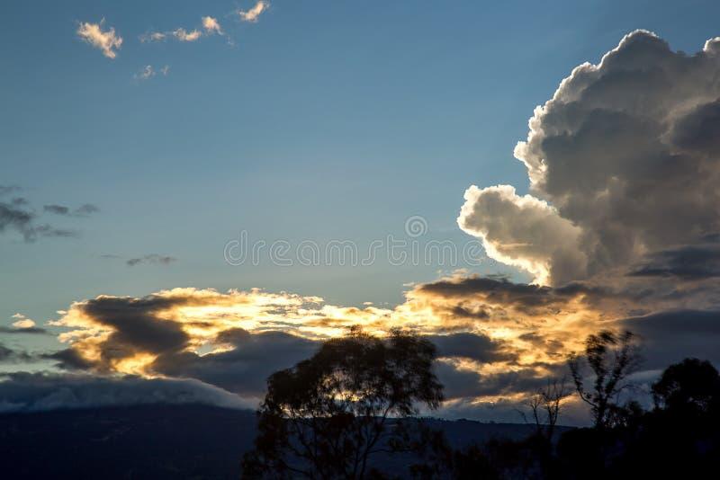 Puesta del sol detrás de las nubes de cúmulo densas fotos de archivo libres de regalías