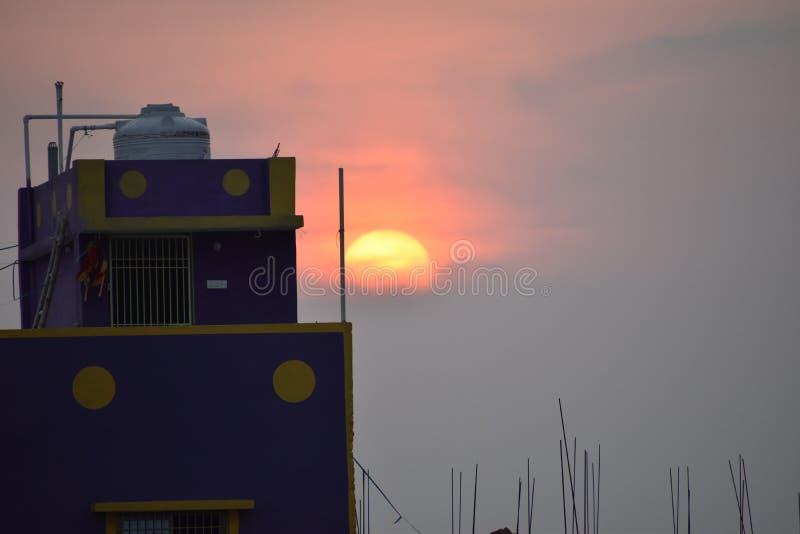 Puesta del sol detrás del edificio en puesta del sol imagenes de archivo