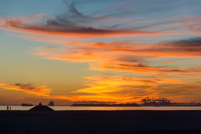 Puesta del sol dramática hermosa sobre las grúas de la playa y del puerto fotografía de archivo libre de regalías