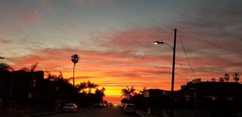 Puesta del sol dramática sobre el Océano Pacífico - opinión de la calle con las palmas fotos de archivo