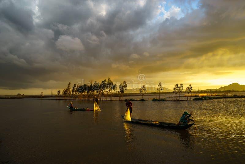 Puesta del sol en campo cultivado con los pescadores que cogen pescados lanzando la jerarquía en An Giang, al sur de Vietnam fotos de archivo