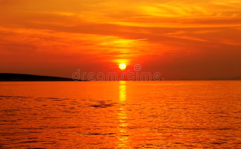 Puesta del sol en color anaranjado vivo en el paisaje marino asombroso en día de verano caliente fotos de archivo