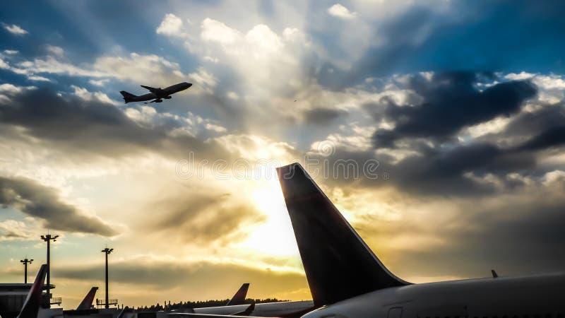 Puesta del sol en el aeropuerto con una cola y un despegue del aeroplano fotografía de archivo libre de regalías