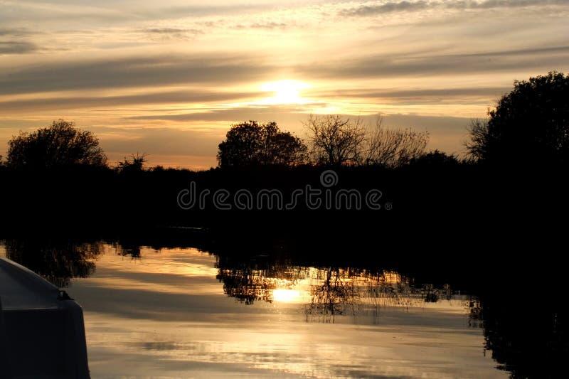 Puesta del sol en el dique Norfolk Broads de la flota imagen de archivo