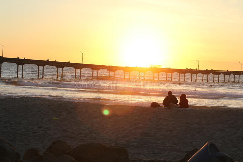 Puesta del sol en el embarcadero en playa del océano foto de archivo libre de regalías
