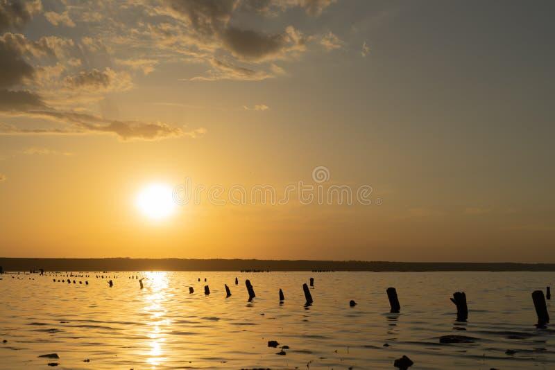 Puesta del sol en el Kuyalnik Liman odessa ucrania Los registros viejos son visibles del agua - los restos de un embarcadero anti fotos de archivo