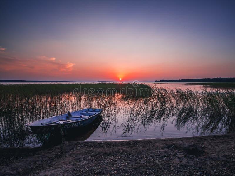 Puesta del sol en el lago, barco de pesca en la orilla fotografía de archivo