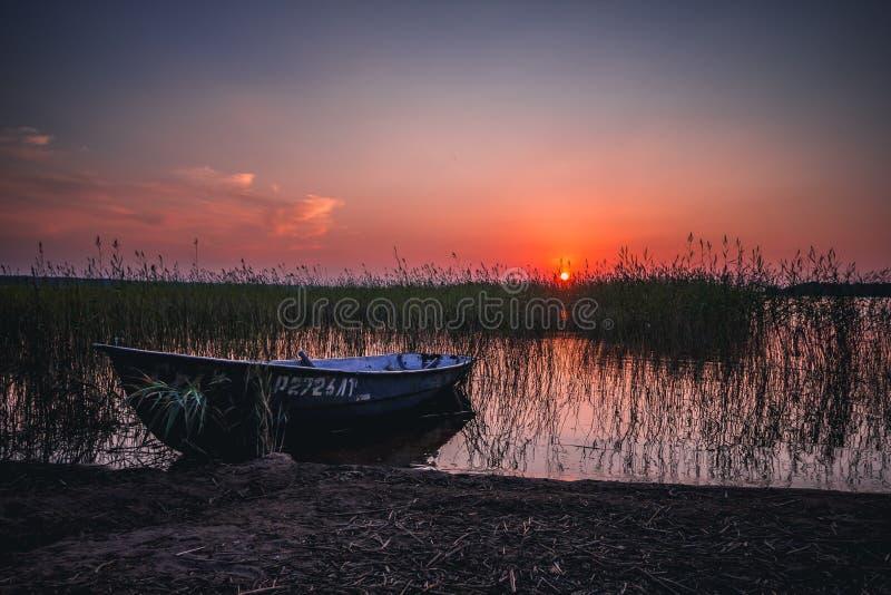 Puesta del sol en el lago, barco de pesca en la orilla imágenes de archivo libres de regalías