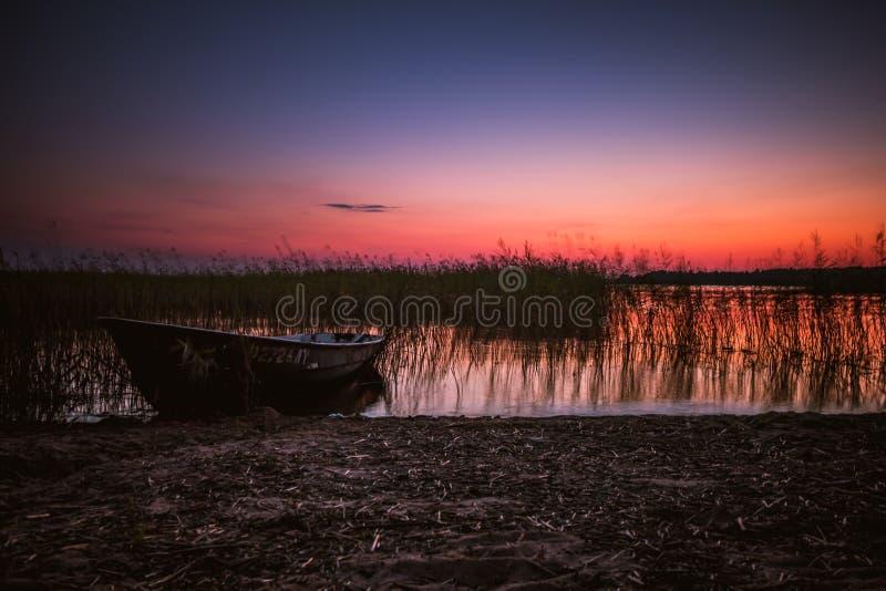 Puesta del sol en el lago, barco de pesca en la orilla fotografía de archivo libre de regalías