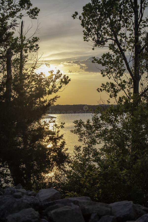 Puesta del sol en el lago de la roca de la tabla foto de archivo libre de regalías