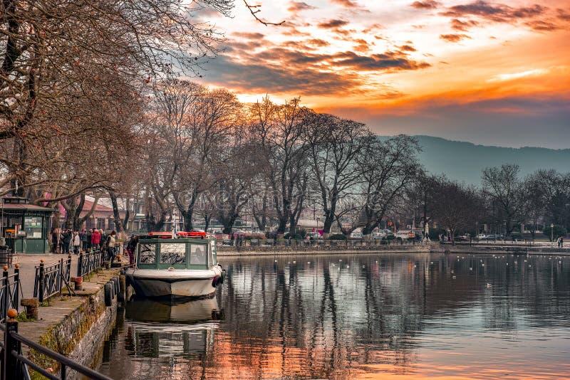 Puesta del sol en el lago Pamvotis Barco atracado listo para transferir a gente a la pequeña isla Grecia fotografía de archivo libre de regalías