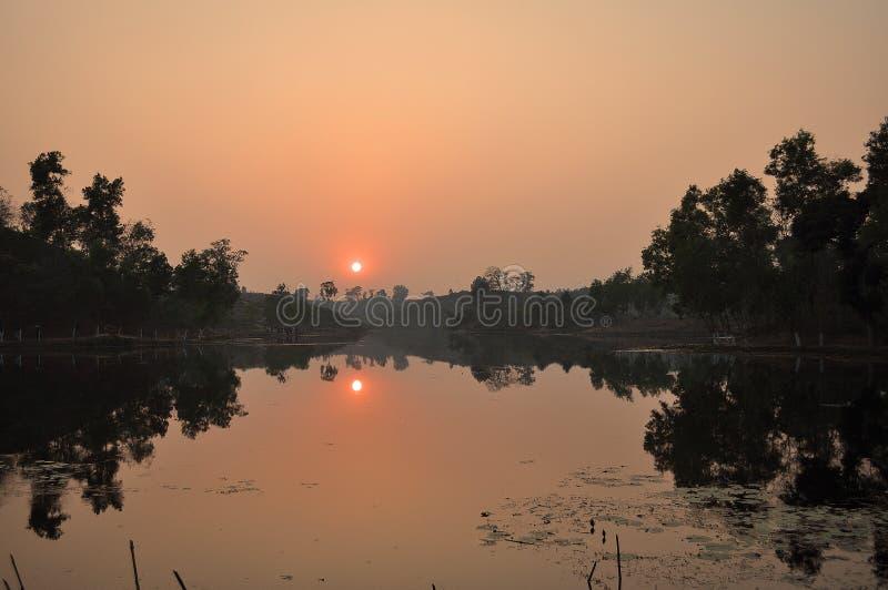 Puesta del sol en el lago y la colina imagenes de archivo