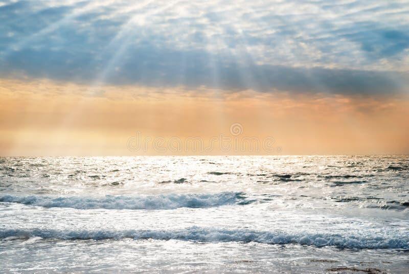 Puesta del sol en el mar azul con las ondas imagen de archivo libre de regalías