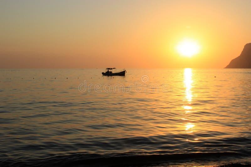 Puesta del sol en el mar con el barco fotos de archivo