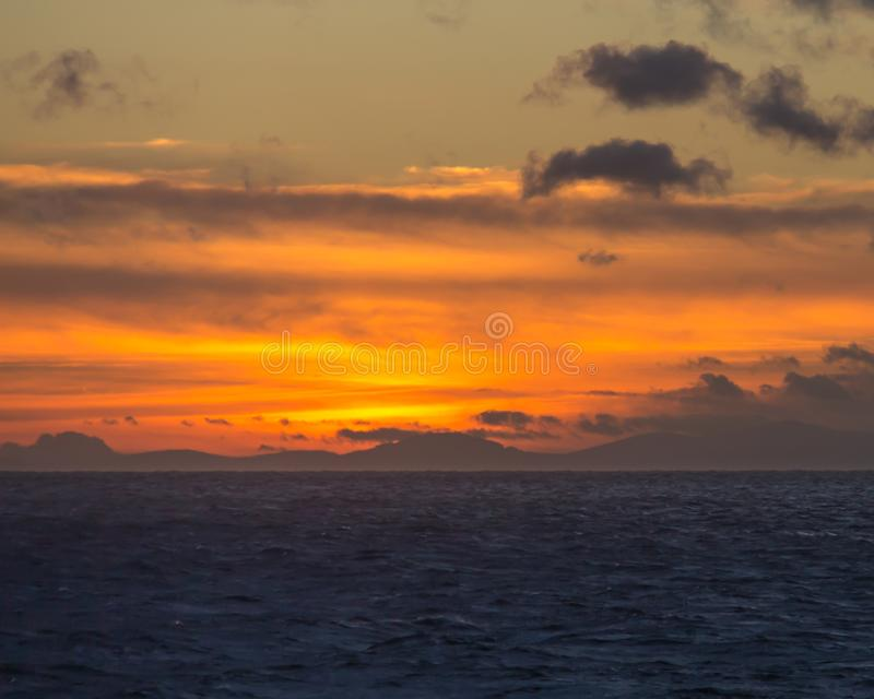 Puesta del sol en el mar con las montañas en el fondo foto de archivo libre de regalías