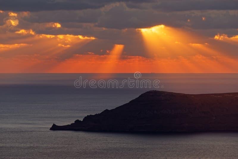 Puesta del sol en el mar con los rayos y la silueta de la isla fotografía de archivo libre de regalías