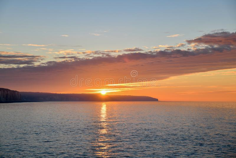 Puesta del sol en el Océano Atlántico en Normandía y reflexión en un agua foto de archivo
