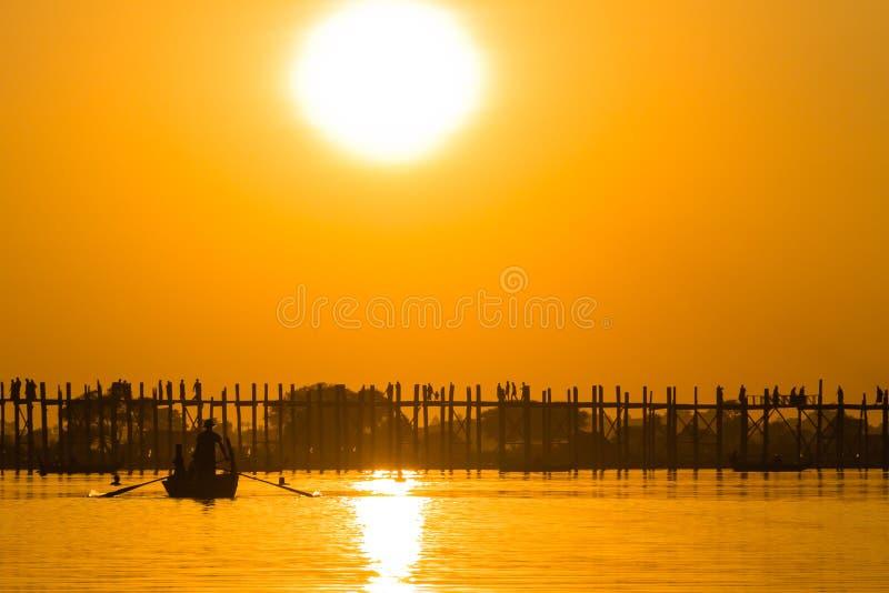 Puesta del sol en el puente del Teakwood de U Bein, Amarapura en Myanmar (Burmar imágenes de archivo libres de regalías
