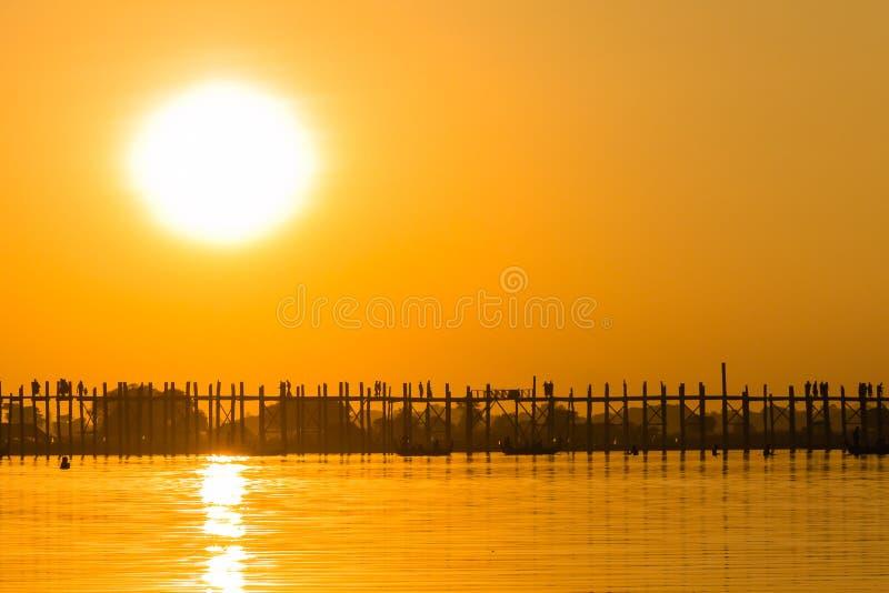 Puesta del sol en el puente del Teakwood de U Bein, Amarapura en Myanmar (Burmar foto de archivo
