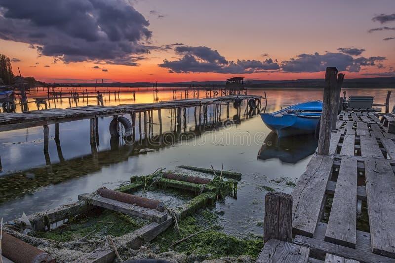 Puesta del sol en el puerto con los embarcaderos y el barco de madera foto de archivo libre de regalías