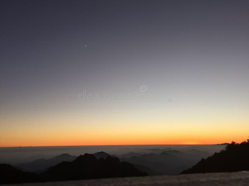 Puesta del sol en el soporte Huangshan en China con la luna en el cielo imagenes de archivo