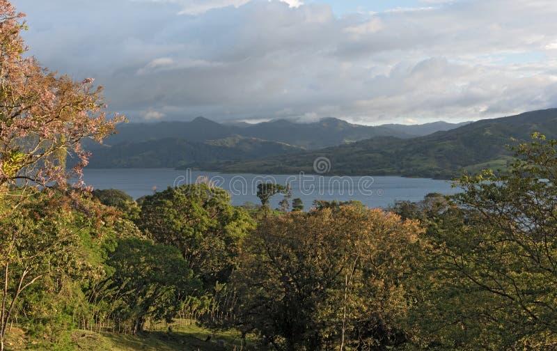 Puesta del sol en el temporal de lluvia en el lago Arenal en Costa Rica fotografía de archivo libre de regalías