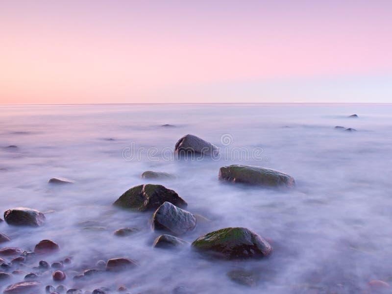 Puesta del sol en la costa rocosa del mar Velocidad de obturador baja para el nivel del agua liso y el efecto soñador foto de archivo libre de regalías