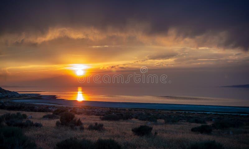 Puesta del sol en la isla del antílope en el Great Salt Lake fuera de la ciudad, oscuridad anaranjada colorida sobre un camino co fotografía de archivo libre de regalías