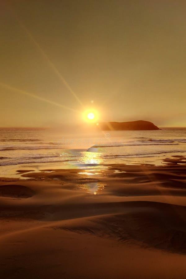 Puesta del sol en la orilla arenosa del Océano Pacífico imagen de archivo
