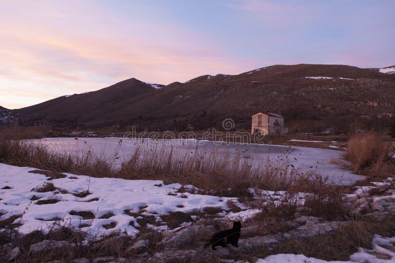 Puesta del sol en la orilla de un lago congelado en Abruzos fotos de archivo