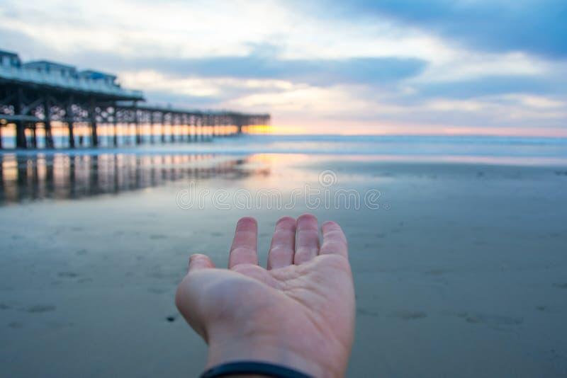 Puesta del sol en la playa con un embarcadero Puesta del sol azul y anaranjada Sun en el pelo imagenes de archivo