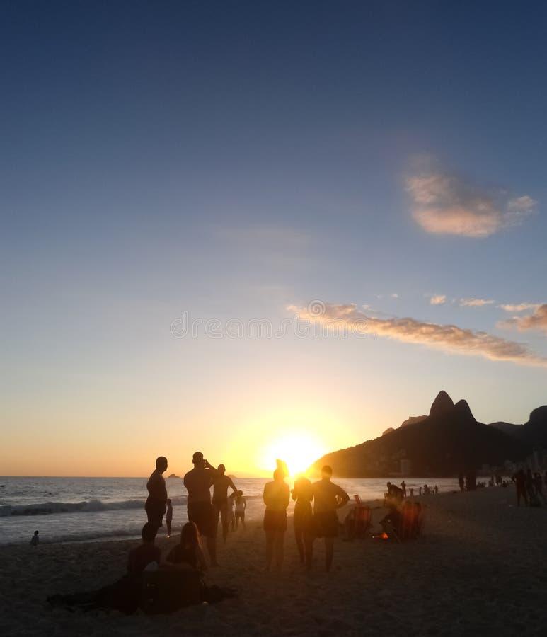 Puesta del sol en la playa de Copacabana en Rio de Janeiro Brazil Gente que tiene vacaciones de la diversión imagen de archivo