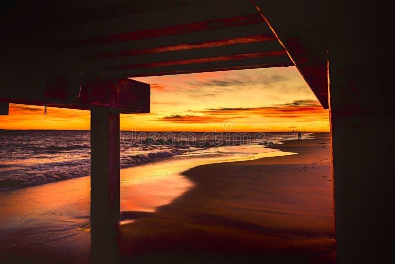 Puesta del sol en la playa debajo de un embarcadero fotos de archivo