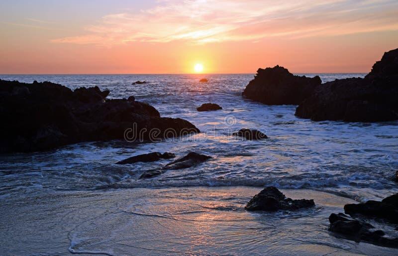 Puesta del sol en la playa en Laguna Beach, California de la ensenada de maderas imagenes de archivo