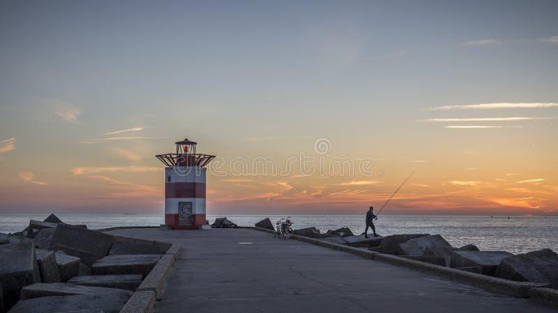 Puesta del sol en la playa La Haya de Scheveningen del faro fotografía de archivo libre de regalías