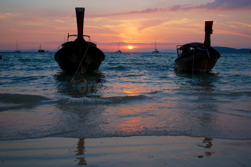 Puesta del sol en la playa tropical con los barcos tailandeses tradicionales fotos de archivo